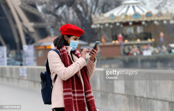 Woman wearing a protective face mask uses her smartphone in front of the Eiffel Tower during the coronavirus outbreak on January 08, 2021 in Paris,...