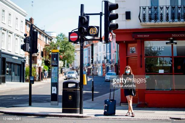 Woman wearing a protective face mask waits at traffic lights in Portobello Market in west London on June 1 following the easing of the lockdown...