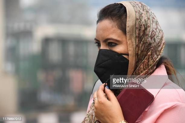 A woman wearing a protective face mask waits for public bus in smoggy conditions in New Delhi on November 4 2019 Millions of people in India's...