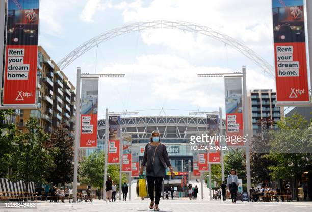 A woman wearing a protective face mask walk down Olympic Way away from Wembley Stadium in London on July 12 the day that Wembley should have hosted...