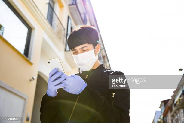woman wearing a protective face mask walking in the street using mobile phone - contact tracing stock pictures, royalty-free photos & images