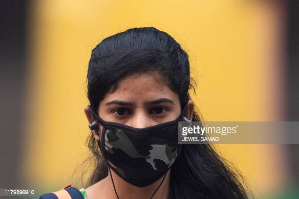Woman wearing a protective face mask walks along a street in smoggy conditions in New Delhi on November 4, 2019. - Millions of people in India's...