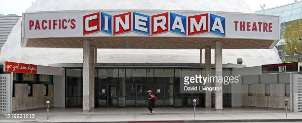 Woman wearing a protective face mask walks by the closed Cinerama Dome theatre during the coronavirus pandemic on April 18, 2020 in Los Angeles,...