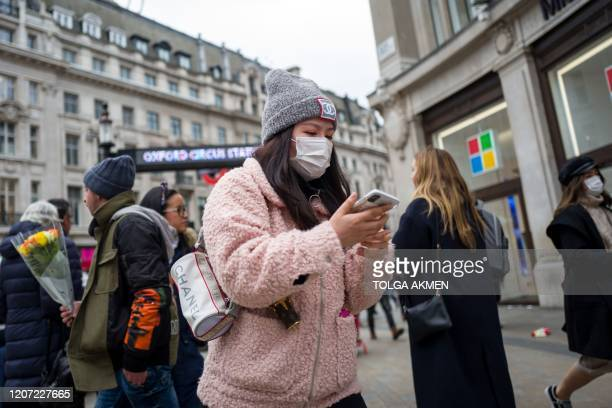 A woman wearing a protective face mask walks down the road at Oxford Circus in central London on March 15 2020