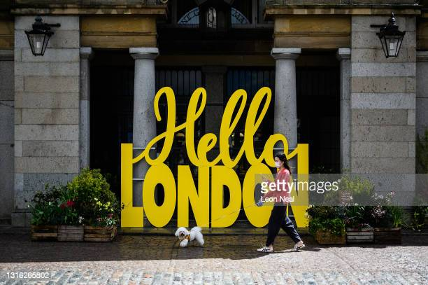 """Woman wearing a protective face mask walks her dog past a large scale installation reading """"Hello London"""" in Covent Garden, on May 04, 2021 in..."""