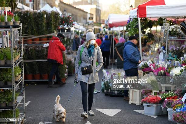 A woman wearing a protective face mask walks her dog through Columbia Road flower market in east London on Mother's Day March 22 2020 Up to 15...