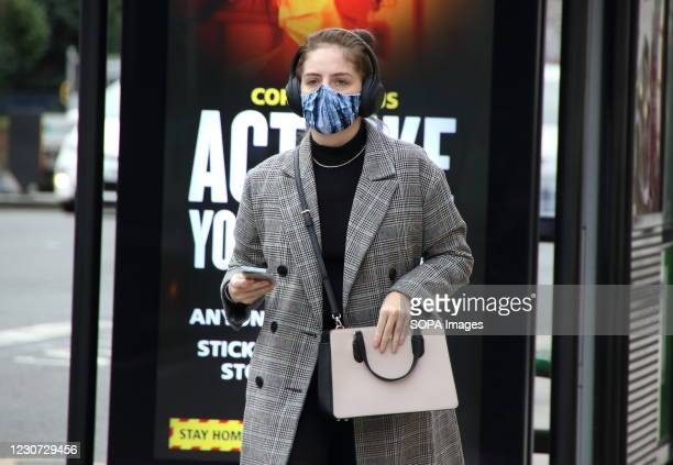 Woman wearing a protective face mask walks in front of an 'Act Like You've got it' warning sign on a London street. England remains under lockdown as...