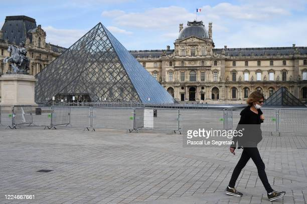 Woman wearing a protective face mask walks in front of the Louvre museum as France is slowly reopening after almost two months of strict lockdown...