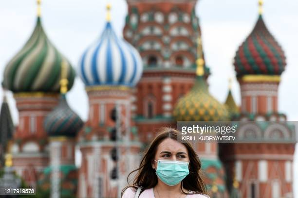 Woman wearing a protective face mask walks in front of the Saint Basil's Cathedral during the annual book fair on the Red Square in downtown Moscow...