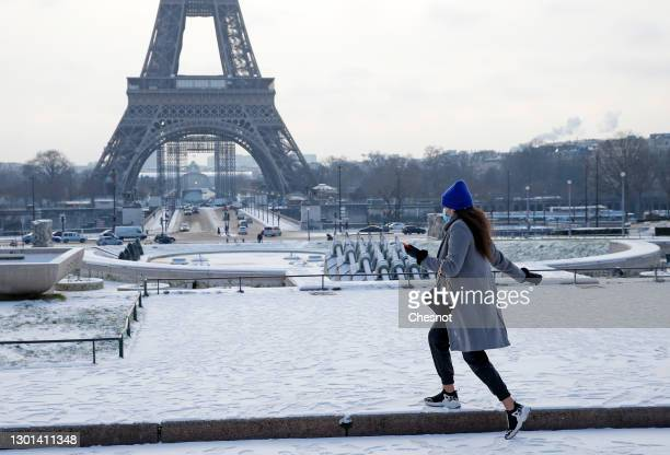 Woman wearing a protective face mask walks in the gardens of Trocadero covered in snow near the Eiffel Tower following a light overnight snowfall on...