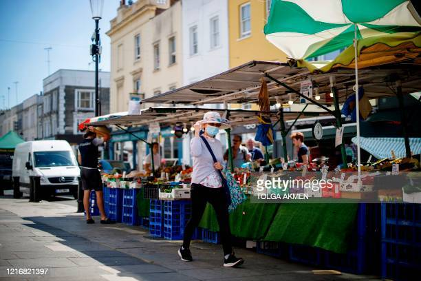 A woman wearing a protective face mask walks past a food stall in Portobello Market in west London on June 1 following the easing of the lockdown...