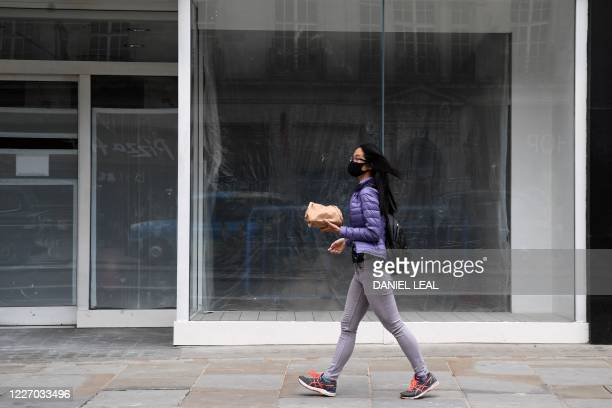 Woman wearing a protective face mask walks past an the windows of empty shop space in London on July 14, 2020. - Britain's economy slumped by almost...