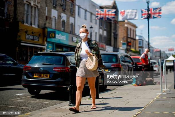 Woman wearing a protective face mask walks past closed shops in Portobello Market in west London on June 1 following the easing of the lockdown...