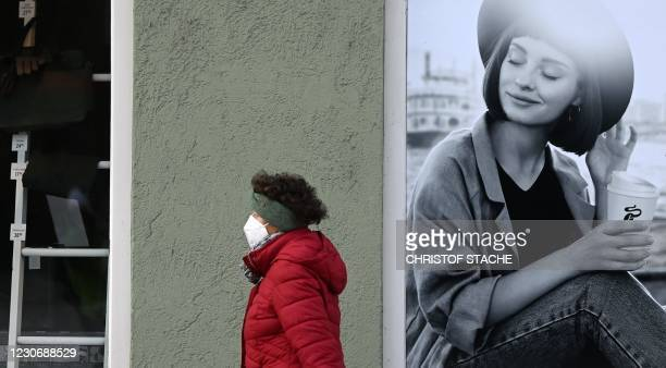 Woman wearing a protective face mask walks past the store windows of a closed shop in the city of Fuerstenfeldbruck, southern Germany, on January 20...
