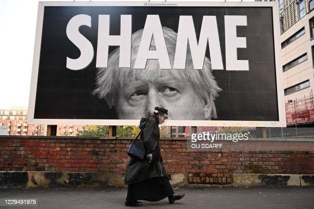 Woman wearing a protective face shield passes a billboard showing Britain's Prime Minister Boris Johnson in Manchester, north-west England on...