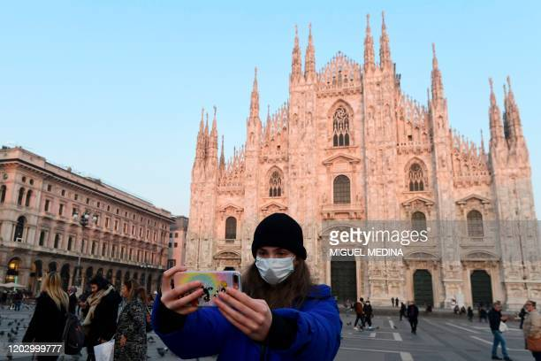Woman wearing a protective facemask takes a selfie picture in the Piazza del Duomo in central Milan, on February 24 following security measures taken...