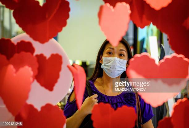 A woman wearing a protective facemask walks behind Saint Valentine's decorations in a shopping mall in Bangkok on February 11 2020 The death toll...