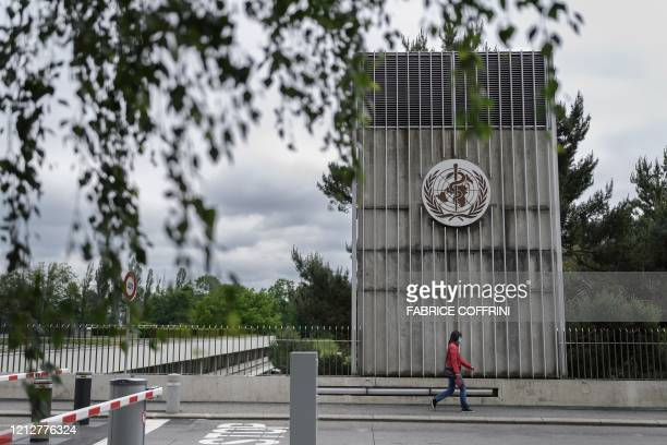 Woman wearing a protective facemask walks underneath a sign of the World Health Organization in Geneva next to their headquarters, on May 12, 2020...