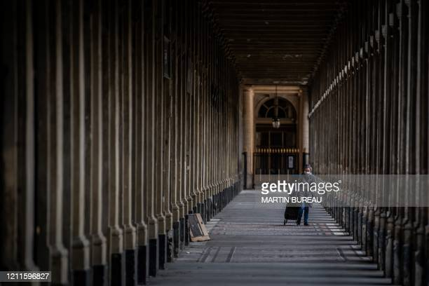 A woman wearing a protective facemasks walks along the Jardin du Palais Royal on May 2 in Paris on the 47th day of a strict lockdown in France aimed...