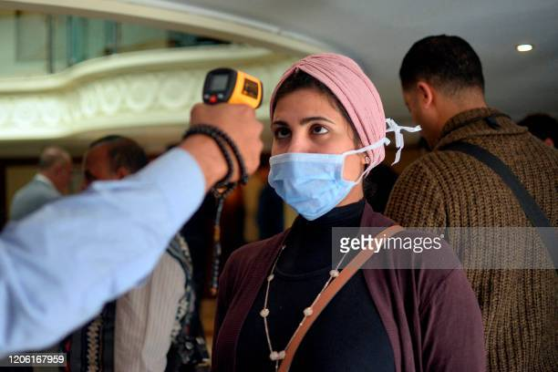 A woman wearing a protective health mask has her body temperature measured at on a touristic river boat in Egypt's southern city of Luxor on March 8...