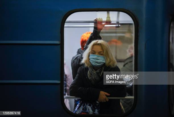 Woman wearing a protective mask as a precaution against the outbreak of Coronavirus rides on a subway in Kiev. The first case of coronavirus in...