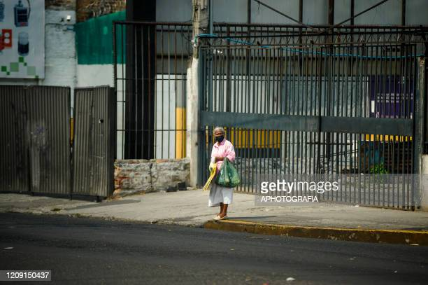 A woman wearing a protective mask awaits for cars to pass by to sell items to collect money for food on April 4 2020 in San Salvador El Salvador On...