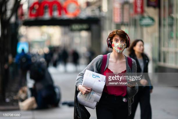 A woman wearing a protective mask carries a toilet paper package on the street on March 13 2020 in New York City President Donald Trump is expected...