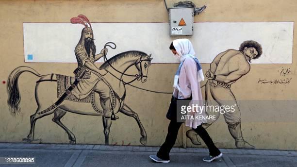 Woman, wearing a protective mask due to the COVID-19 coronavirus pandemic, walks past a graffiti depicting the legendary Persian hero Rustam riding...