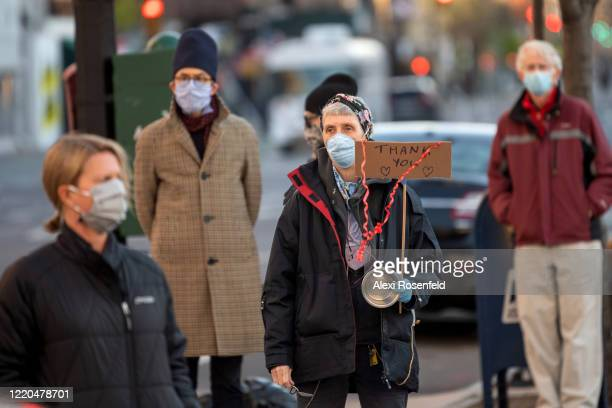 A woman wearing a protective mask holds a 'thank you' sign during the 7PM nightly cheer in honor to healthcare workers in front of the Lenox Health...