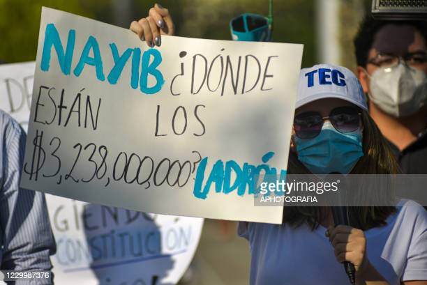 Woman wearing a protective mask holds up a sign asking to know how a 3 billion USD loan was utilized by the government during a protest against...
