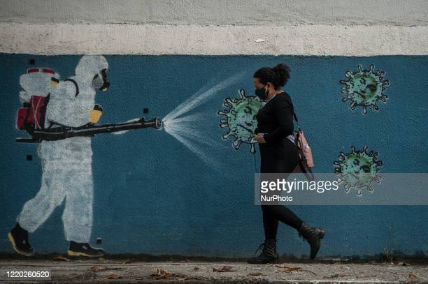 A woman wearing a protective mask is seen walking in front of graffiti by collectives of artists Nogenta and contraconsiencia in the neighborhood of...