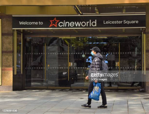 A woman wearing a protective mask is seen walking past the recently closed Cineworld Empire on Leicester Square While cinemas in the UK have reopened...
