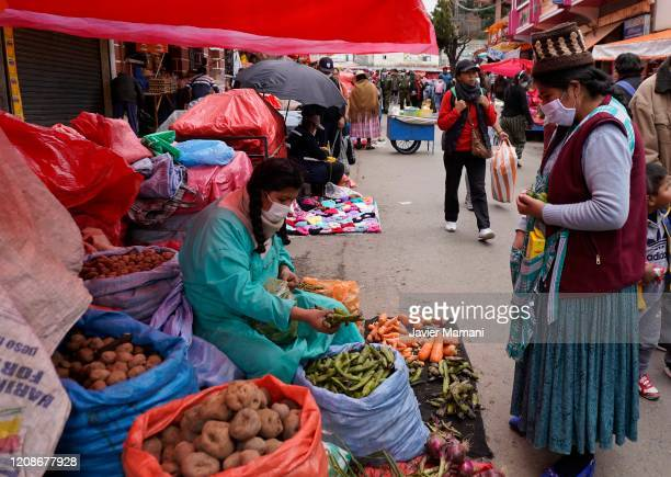 Woman wearing a protective mask keep her distance as buying food on March 30, 2020 in La Paz, Bolivia. Bolivia has established a blockade to prevent...