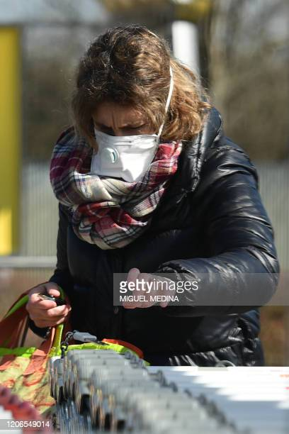 A woman wearing a protective mask picks a cart as he arrives to shop at a supermarket in Codogno southeast of Milan on March 11 2020 a day after...