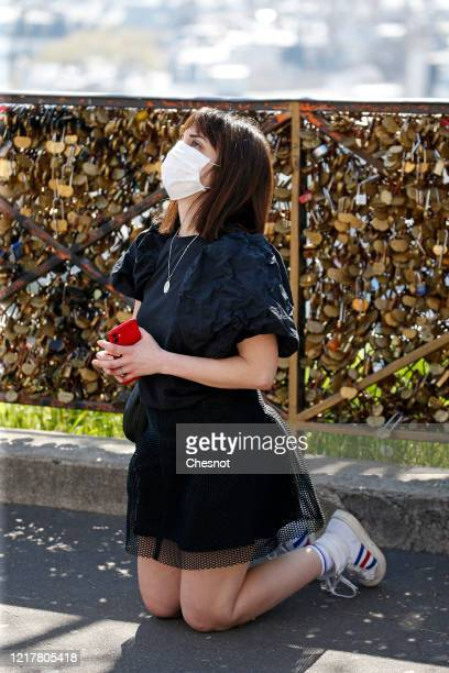 Woman wearing a protective mask prays during a blessing ceremony of the city of Paris by Archbishop of Paris Michel Aupetit in front of Sacre-Coeur...