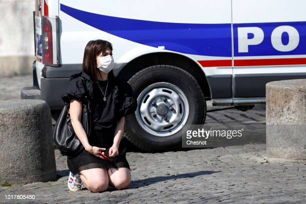 A woman wearing a protective mask prays next to a police truck during a blessing ceremony of the city of Paris by Archbishop of Paris Michel Aupetit...