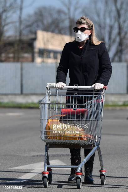 A woman wearing a protective mask pushes her cart as she arrives to shop at a supermarket in Codogno southeast of Milan on March 11 2020 a day after...