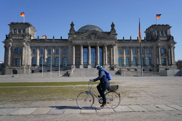 A woman wearing a protective mask rides a bicycle past the Reichstag where inside the Bundestag a massive federal financial aid package is expected...