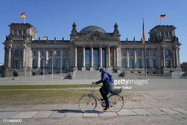 Woman wearing a protective mask rides a bicycle past the Reichstag where, inside the Bundestag, a massive federal financial aid package is expected...