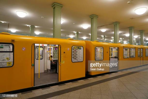 Woman wearing a protective mask sits in a nearly deserted U-Bahn subway train at Alexanderplatz station, which at that time of day would usually be...