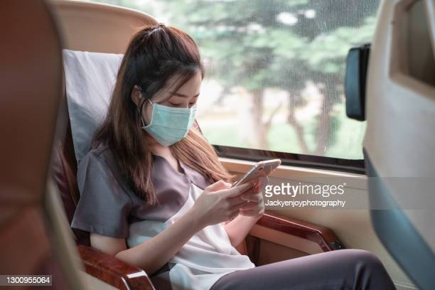 a woman wearing a protective mask sitting on a bus or train an use smartphone - manager stock pictures, royalty-free photos & images