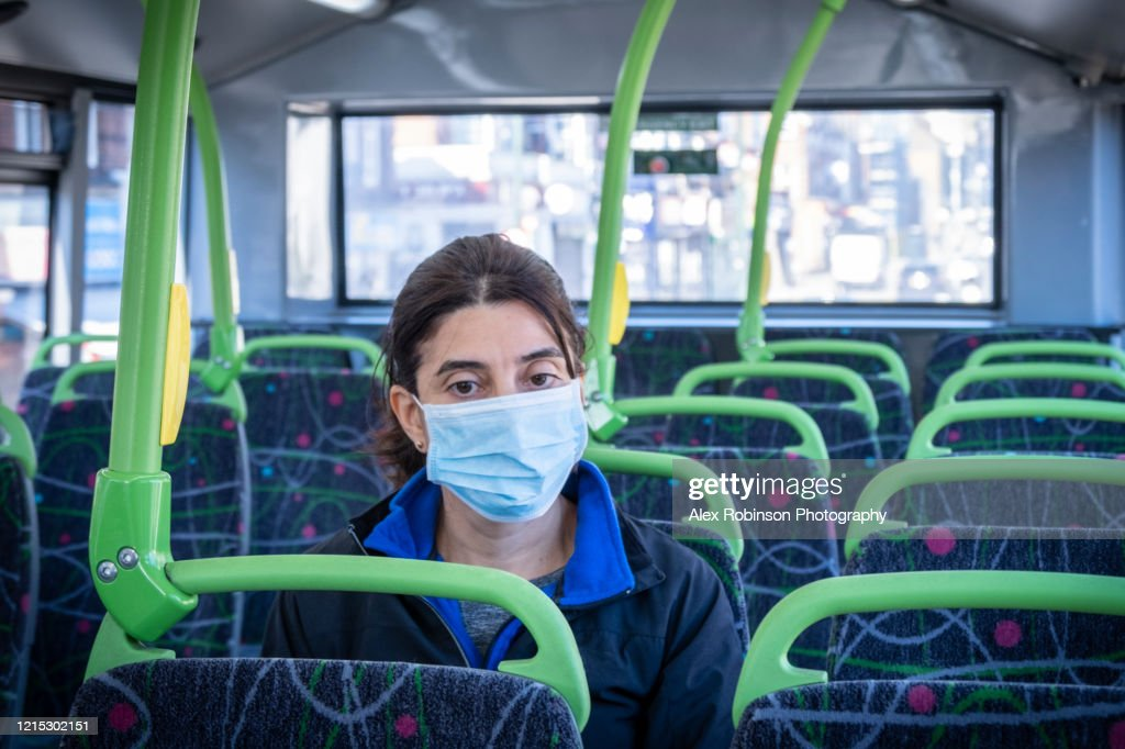 A woman wearing a protective mask sitting on a bus : Stock Photo