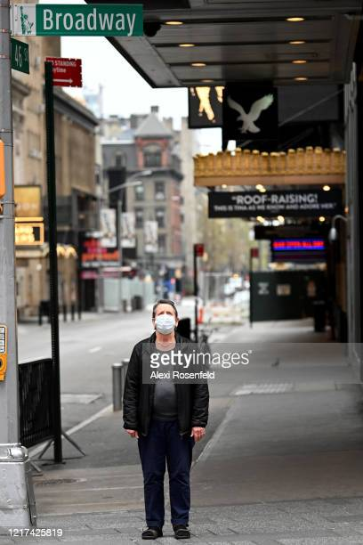 A woman wearing a protective mask stands alone on the corner of Broadway and 46th Street in Times Square amid the coronavirus pandemic on April 05...