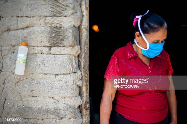 A woman wearing a protective mask stands outside of her adobe house next to a bottle with alcohol as part of her COVID19 preventive measures during...