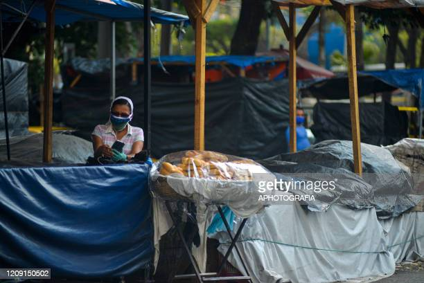 A woman wearing a protective mask stands waiting for customers as she sells bread on April 3 2020 in San Salvador El Salvador On March 21st President...