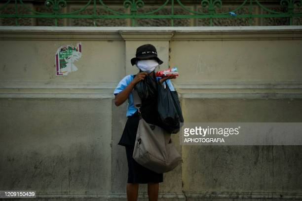 A woman wearing a protective mask stands waiting for people to pass by to sell first necessity items to collect money for food on April 4 2020 in San...