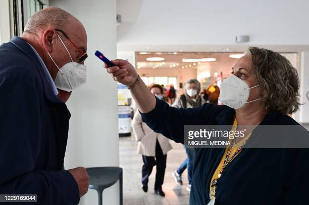 Woman wearing a protective mask takes the temperature of a man wearing a protective mask arriving at the Guido Salvini hospital in Garbagnate...