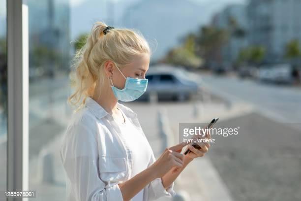 frau trägt eine schutzmaske mit handy - bucht stock-fotos und bilder