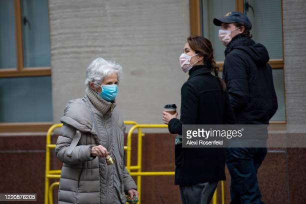 A woman wearing a protective mask walks down the street ringing a bell for healthcare workers during the 7PM nightly cheer amid the coronavirus...