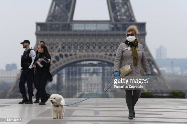 Woman wearing a protective mask walks her dog on the Esplanade du Trocadero square in front of the Eiffel Tower the second day after the announcement...